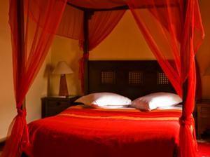 dormitor crem cu un baldachin cu draperii rosii