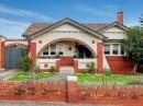 casa cu arcada la intrare model rustic taranesc acoperita cu tigla cu gard din caramida